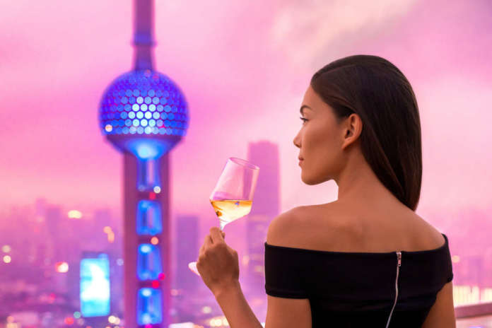 Elegant asian woman and skyline view of Shangai in Sunset