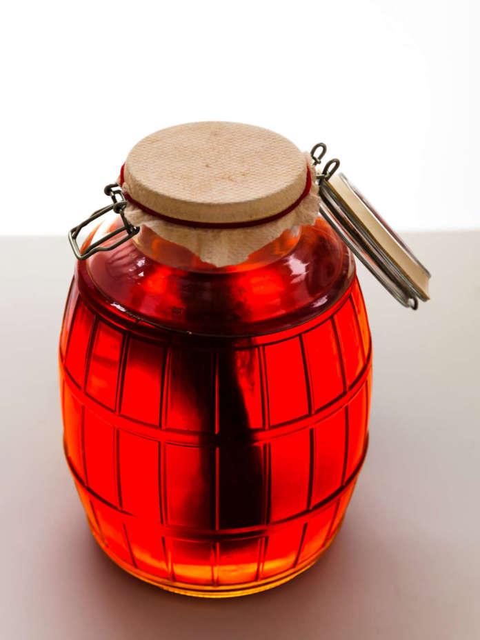Scoby galleggia verticalmente in una jar con kombucha fermented tea.