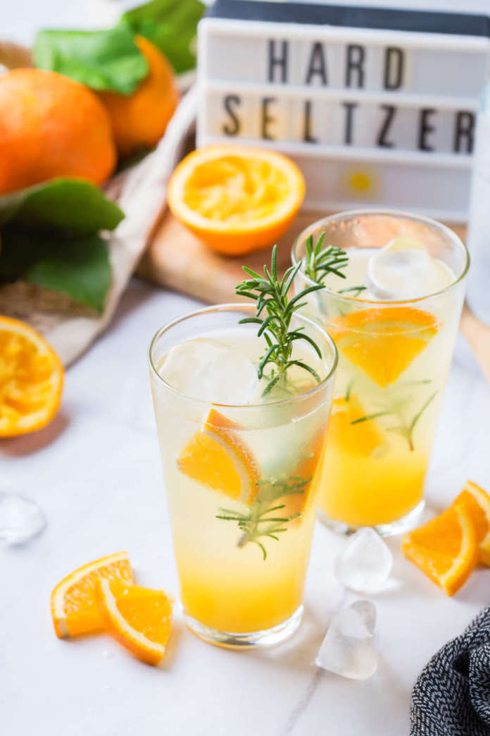 Hard seltzer cocktail with orange, rosemary and ice on a table. Summer refreshing beverage, drink on a white table